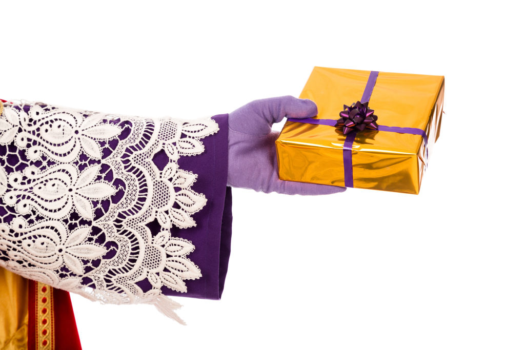 Hand of sinterklaas  with gift . typical Dutch character part of a traditional event celebrating the birthday of Sinterklaas (Santa Claus) in december.